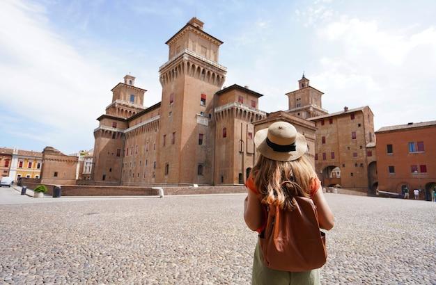 Travel in italy. rear view of traveler girl walking towards este castle (castello estense) of ferrara, italy.