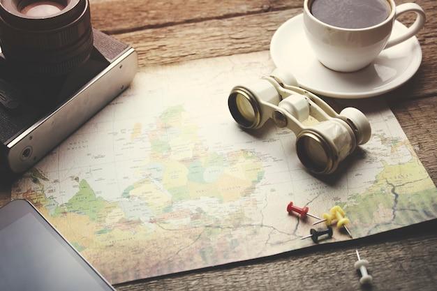 Предметы для путешествий - бинокль, карта, кофе, фотоаппарат и телефон.