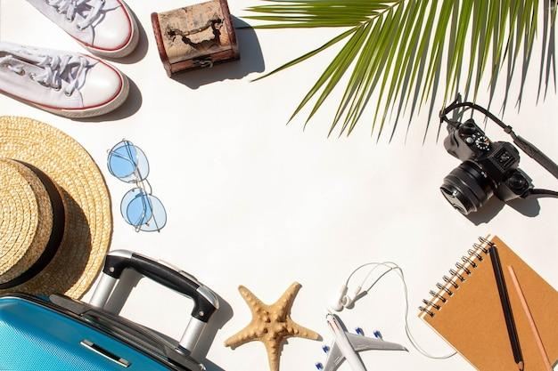 旅行アイテムフレーム。青いスーツケース、ヤシの葉、おもちゃの飛行機、カメラ、ヤシの葉