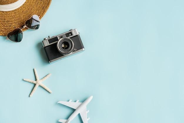 青い机の上の旅行アイテム。夏、休日、旅行のコンセプトを計画しています。フラットレイとコピースペース