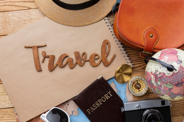Travel items on wooden background top view