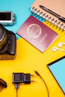 Дорожный комплект из фотоаппарата, бумажного блокнота, смартфона и паспорта на двухцветном фоне