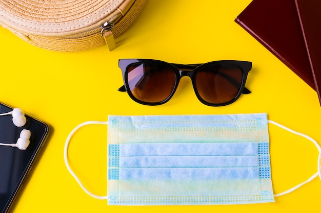 Travel kit and protective mask on bright yellow background top view