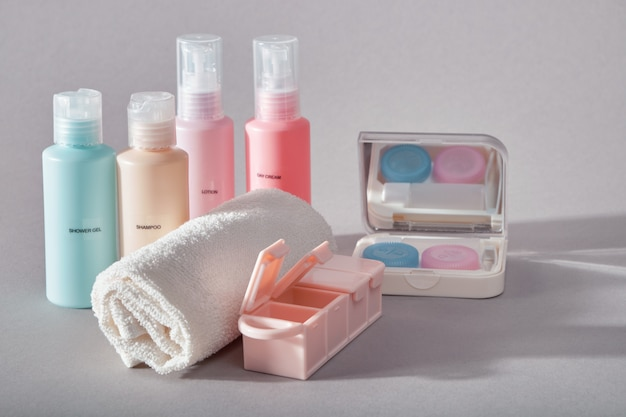 Travel kit. set of four small plastic bottles for cosmetic products, kit for contact lenses, pill organizer, towel.
