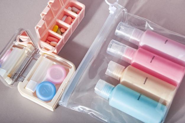 トラベルキット。化粧品用の小さなペットボトル4本、コンタクトレンズ用キット、ピルオーガナイザーのセット。