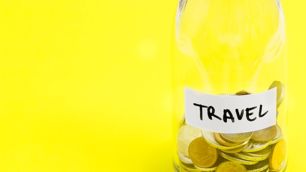 Travel label on coins jar against yellow background