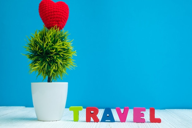 Travel letters text and notebook paper and little tree on wood