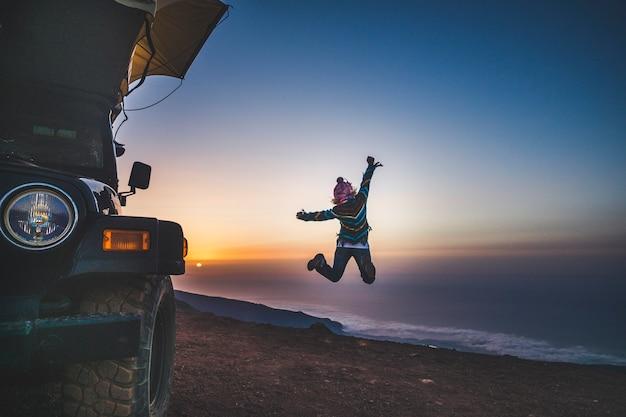 旅行のライフスタイルと人々の幸せの探求-後ろからジャンプして山の頂上で自由と美しい夕日を楽しんでいる女性-別の休暇と冒険のために駐車されたテント付きの車