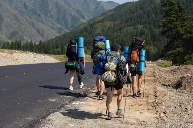 旅行ライフスタイルとサバイバルコンセプトバックパックを持った観光客は山への道に沿って行きます