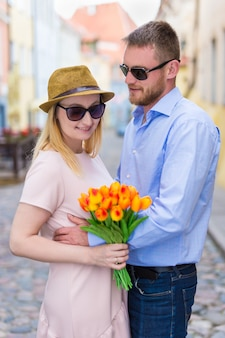 Travel and love concept - young man giving flowers to his girlfriend or wife