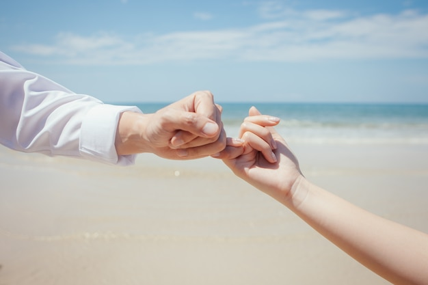 Travel lovers hand in hand each other and pinky swear