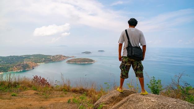 Phahindum 관점에서 풍경 보기를 보기 위해 바위에 서 있는 여행 남자 사진사 태국 푸켓에서 인기 있는 랜드마크 프롬텝 케이프 naiharn 해변과 yanui 해변을 보기 위한 관점 놀라운 보기입니다.