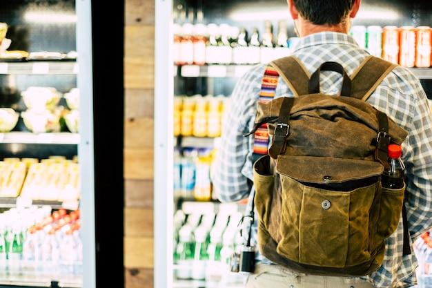 出発前に軽食や飲み物を選択する自動飲料店の前で後ろから見た旅行者、またはビジネスや休暇旅行を開始する-バックパックで後ろから見た