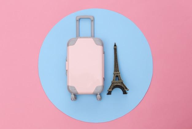 旅行のミニマリズム。ミニプラスチック製の旅行スーツケースと青い円とピンクの背景にエッフェル塔の小像。最小限のスタイル。上面図、フラットレイ
