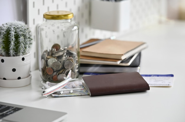 Travel money savings in a glass jar with passport, ticket and map on office desk.