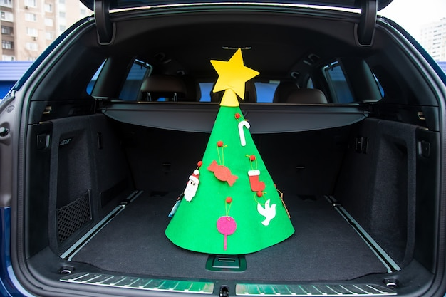 Travel for new year holidays. a felt christmas tree decorated with toys and a star stands in the center of the empty trunk of a modern crossover. close-up, soft focus