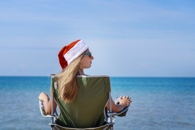 Travel on new years eve on beach by sea girl in christmas hat is sunbathing in sun woman