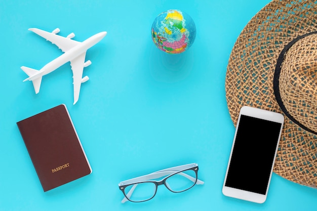 Travel objects and accessories on blue background with passport  and plane.