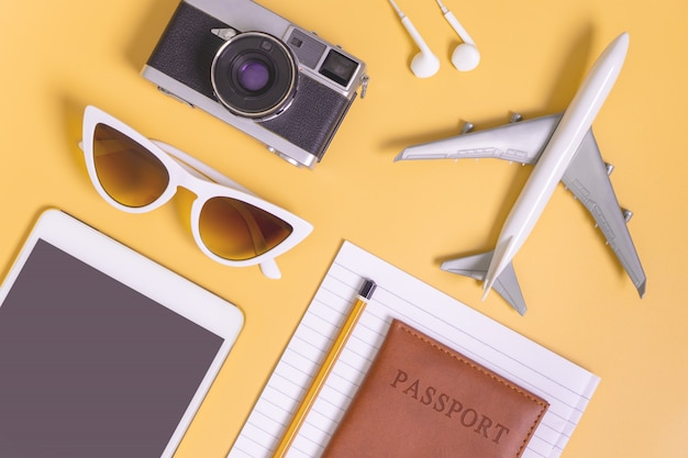Travel objects flat lay on yellow background for travel concept