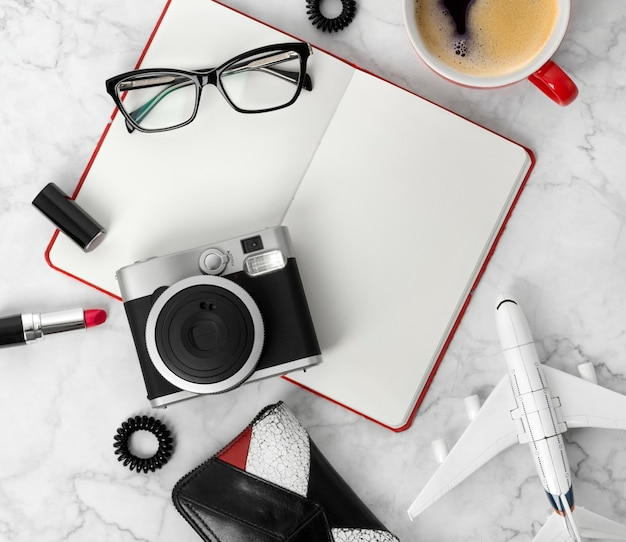Travel objects flatlay on white wooden table with copy space. planner, glasses, cup of coffee, camera, ear rings, hair tie, comb and lipstick at stylish marble table