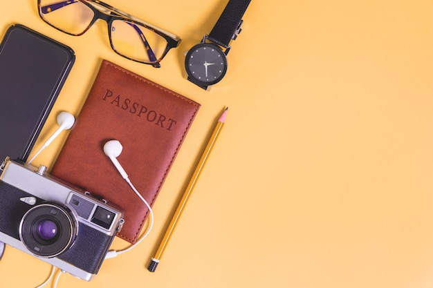 Travel objects flatlay on yellow background with copy space