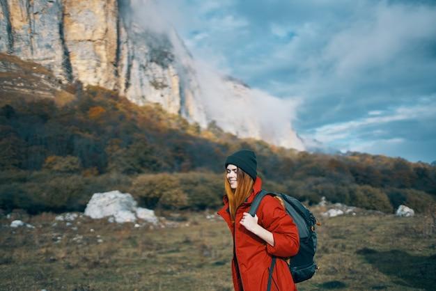 青い空と高い山々にバックパックの帽子をかぶったジャケットを着た女性の旅