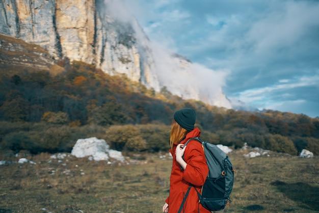 青空と高い山々にバックパックの帽子をかぶったジャケットを着た女性の旅