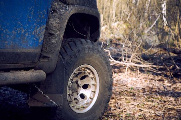 Путешествуйте по бездорожью по лесной дороге на синей машине 4х4. внедорожник 4х4 весь грязный