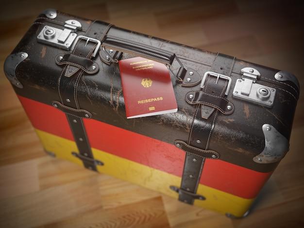 旅行または移民の概念。ドイツのパスポートとドイツの旗が付いているスーツケース3dイラスト