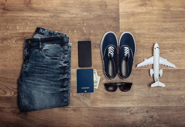 Концепция путешествий или туризма. джинсы, стодолларовые купюры, кроссовки, смартфон, паспорт, солнцезащитные очки, самолет на деревянном полу. вид сверху. плоская планировка