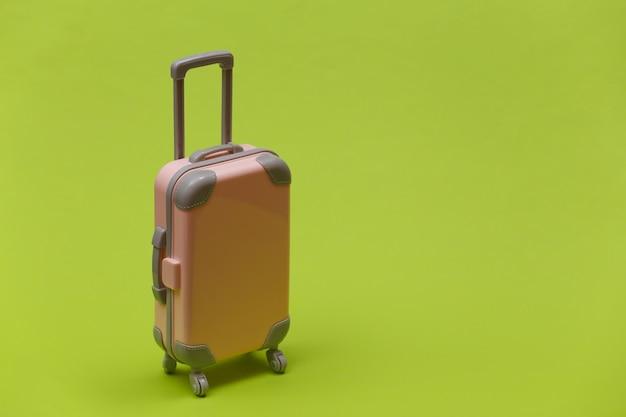 Концепция путешествия или поездки. мини-пластиковый дорожный чемодан на зеленом фоне. минималистичный стиль