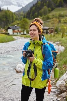 Concetto di viaggio e attività all'aperto. viandante femminile adorabile ottimista cammina dal piccolo ruscello di montagna