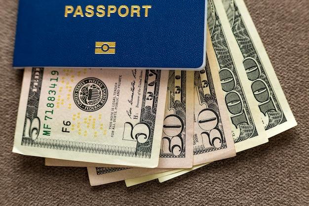 Путешествуйте пасспорт и деньги, счеты банкнот американских долларов на предпосылке космоса экземпляра, взгляд сверху. концепция проблемы путешествий и финансов.