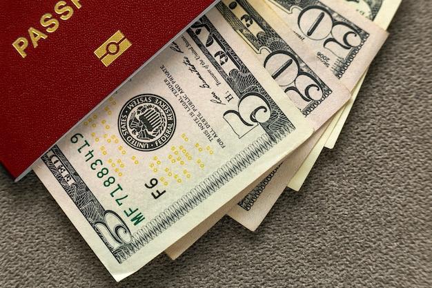Путешествуйте паспорт и деньги, счеты банкнот американских долларов на взгляд сверху космоса экземпляра. концепция проблемы путешествий и финансов.