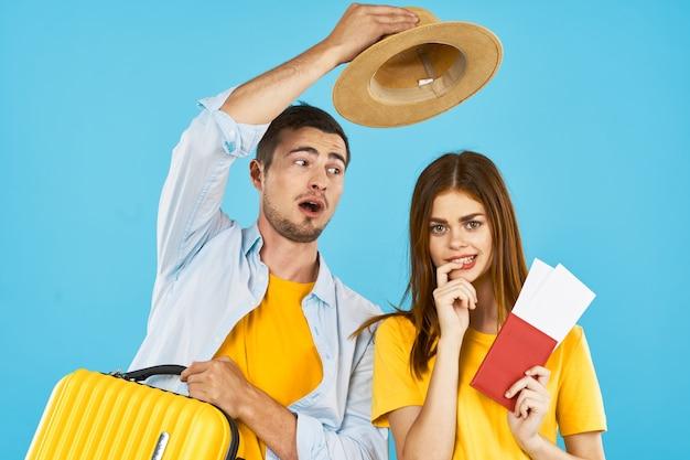 旅行パスポートと飛行機のチケット休暇荷物休暇男と女の冒険旅行青い背景