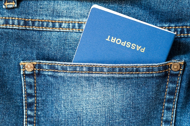 Travel passport  in a pocket of blue jeans close up