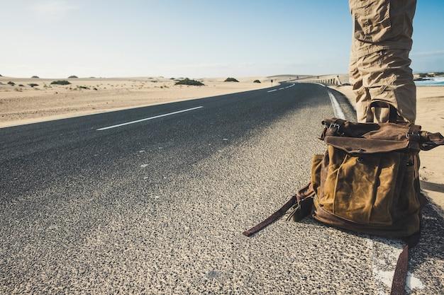 Путешествующие люди и концепция приключенческого образа жизни с крупным планом человека, стоящего на длинной дороге с модным рюкзаком в ожидании машины, чтобы разделить поездку