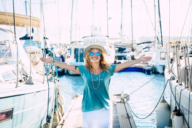 旅行の人々と幸せな大人の若い女性が腕を広げて季節を楽しむ夏休み休暇のコンセプト