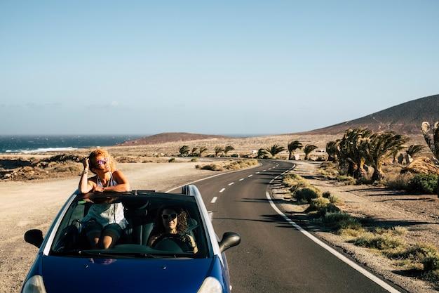 2人の女性がコンバーチブルカーを運転して夏休みを楽しむ、旅行者の自由なライフスタイルのコンセプト