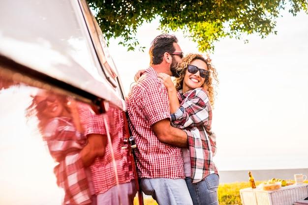 旅行の人々は、赤い古いバン車と一緒に屋外で抱き合って楽しむ