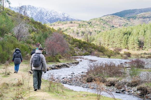 Путешествия, люди, путешествующие, походы в горы у реки, группа туристов, смотрящих на панорамный пейзаж.