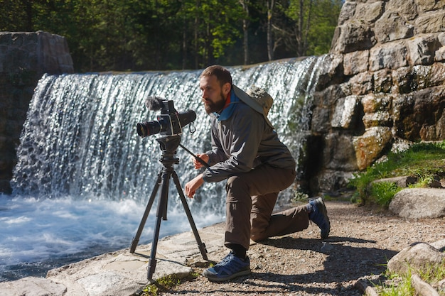 Travel photographer bearded man with professional film camera on tripod shooting mountain landscape in waterfall background. hiker tourist professional photography shooting, filming backstage