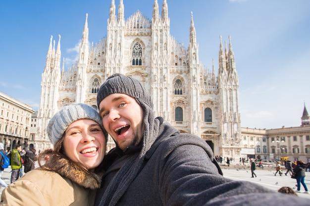 여행 사진과 사람들의 개념 행복한 커플이 두오모 광장의 밀라노에서 자화상을 찍는다