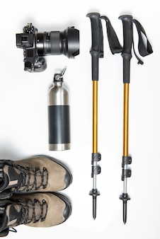 Travel photography kit. a pair of hiking or trekking poles sticks, camera, bottle and trekking boots isolated on