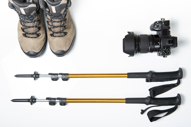 Travel photography kit. a pair of hiking or trekking poles sticks, camera and trekking boots isolated on