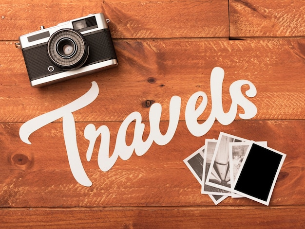 Travel photos with camera on wooden table