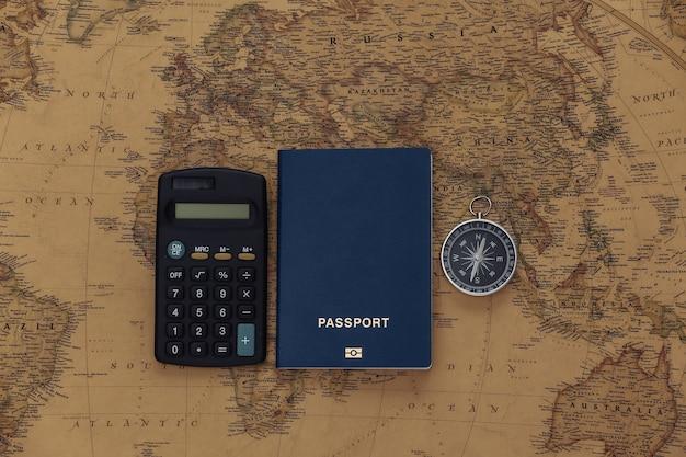 旅行の計画。古い地図上の電卓、コンパス、パスポート。旅行、冒険の概念