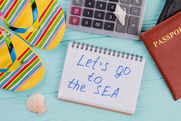 여권, 샌들, 계산기가 있는 사무실에서의 여행 계획 개념. 메모장에 적힌 바다로 가자.