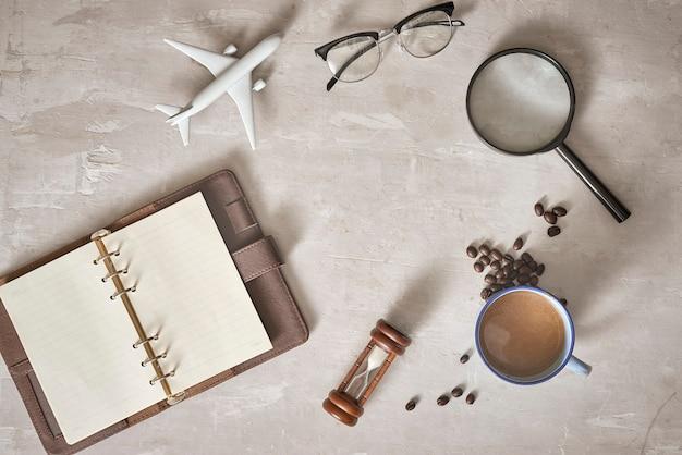 Предпосылка концепции планирования путешествий. аксессуары для путешественников; увеличительное стекло, солнцезащитные очки, самолет и блокнот на деревянном столе, вид сверху и место для копирования