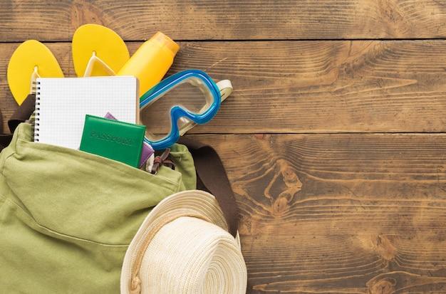 旅行計画のコンセプト。木製テーブルの上の空白のノートブックと旅行者のアクセサリーとフラットレイアウトバックパック